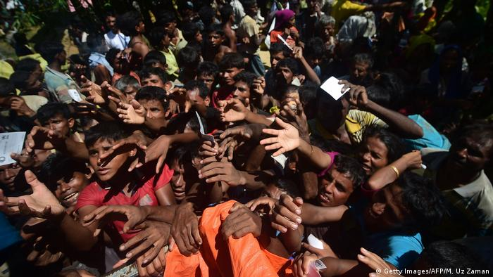 With arms outstretched, Rohingya refugees jostle for relief supplies (Getty Images/AFP/M. Uz Zaman)