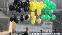 18.10.2017****dpatopbilder - Eine junge Frau befestigt am 18.10.2017 in Berlin Luftballons in den Jamaika-Farben an einem Geländer bei der Parlamentarischen Gesellschaft an der Spree. Union, FDP und Grüne beginnen hier die Sondierungen für eine Jamaika-Koalition. Die Organisation Mehr Demokratie demonstrierte mit der Aktion für bundesweite Volksentscheide im Koalitionsvertrag. Foto: Kay Nietfeld/dpa | Verwendung weltweit
