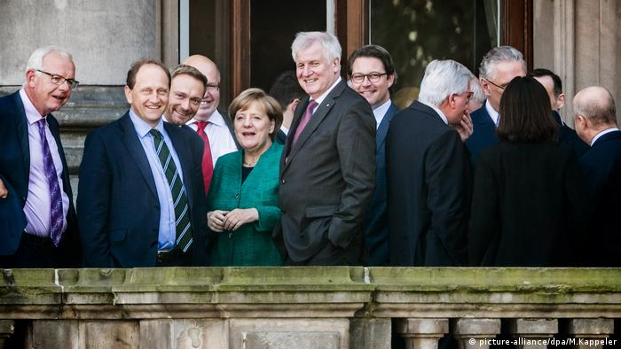 Alexander Graf Lambsdorff stands on a balcony aside Angela Merkel and other top-tier German politicians