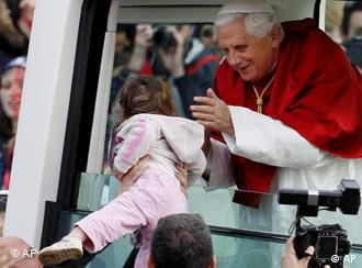 Pope Benedict XVI smiles after he kissed a child from his pope-mobile on his arrival for the Final Mass at Randwick Racecourse during World Youth Day in Sydney, Australia, Sunday, July 20 2008.(AP Photo/Rob Griffith)