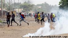 People running from tear gas during protests in Togo's capital Lome