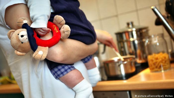 Symbolbild Frau mit Baby in der Küche beim Kochen (picture-alliance/dpa/J. Woitas)