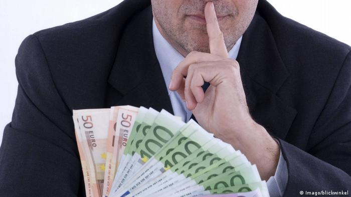 man holding a bundle of money and a finger to his lips