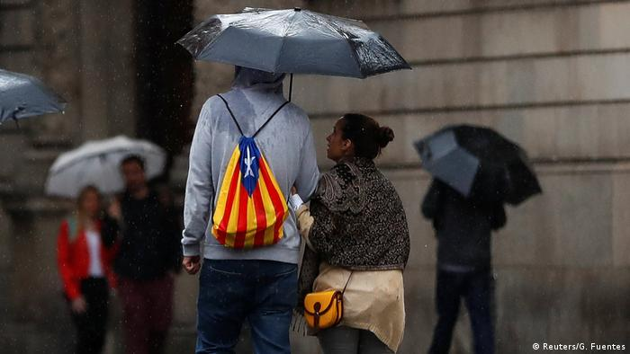 A man with a backpack in the colors of a Catalan separatist flag