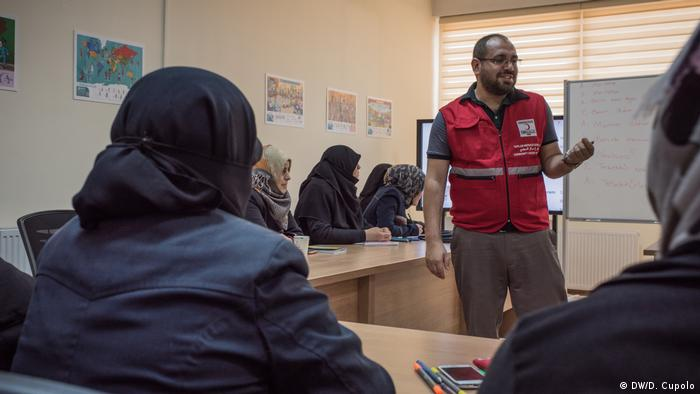 A Turkish language teacher instructs a group of Syrian female students in the Turkish Red Crescent Ankara Community Center