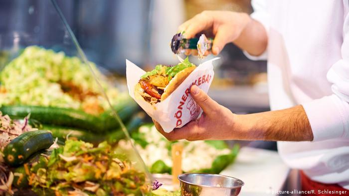 Ein Döner Kebab im Brötchen wird von zwei Händen an einer Theke zubereitet (picture-alliance/R. Schlesinger)