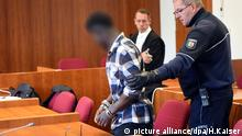 A handcuffed man in court