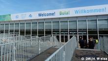 Vorderansicht des Konferenzgebäudes auf der Bonn-Zone in der Blumenwiese der Rheinaue. Die Eingangsgitter sind schon angebracht