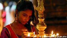 A devotee lights oil lamps at a religious ceremony during the Diwali or Deepavali festival at a Hindu temple in Colombo, Sri Lanka October 18, 2017. REUTERS/Dinuka Liyanawatte