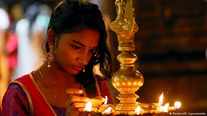 A woman lights oil lamps at a Hindu temple