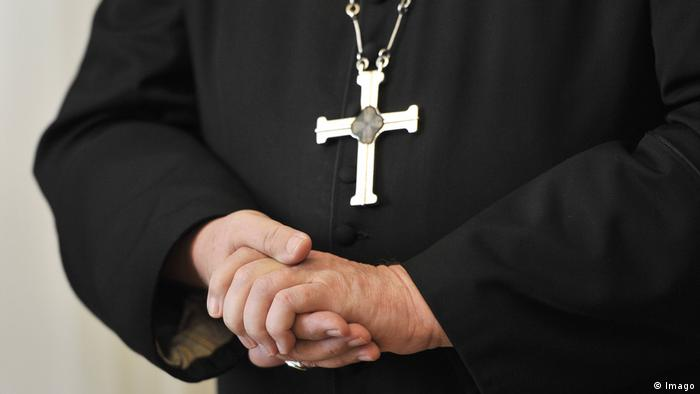 A Catholic priest clasping his hands