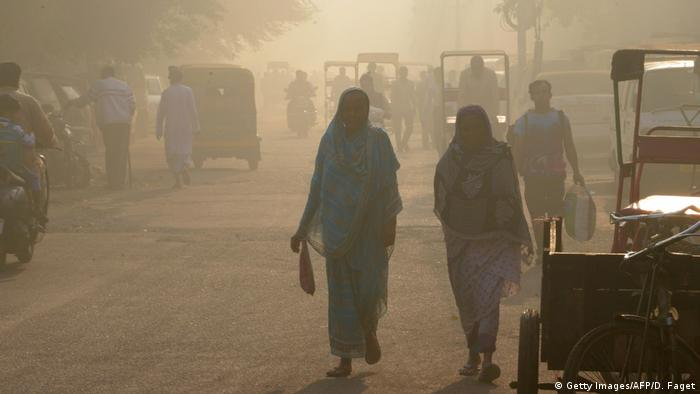Indian commuters walk through the smog in the old quarters of New Delhi