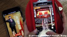 A woman poses as she playing a Tencent's smartphone game called A Great Speech, clap for Xi Jinping in Beijing, Friday, Oct. 20, 2017. Ordinary young Chinese may not have paid close attention to Xi Jinping's 3-and-a-half hour marathon speech this week, but they're happy to applaud the president in the newest viral phenomenon to sweep China's internet. (AP Photo/Andy Wong)  