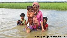 Rohingya refugee Khalida, a mother of three children, wade across a canal near the no man's land area between Bangladesh and Myanmar (Getty Images/AFP/T. Mustafa)