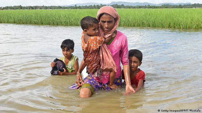 Rohingya refugee Khalida, a mother of three children, wade across a canal near the no man's land area between Bangladesh and Myanmar