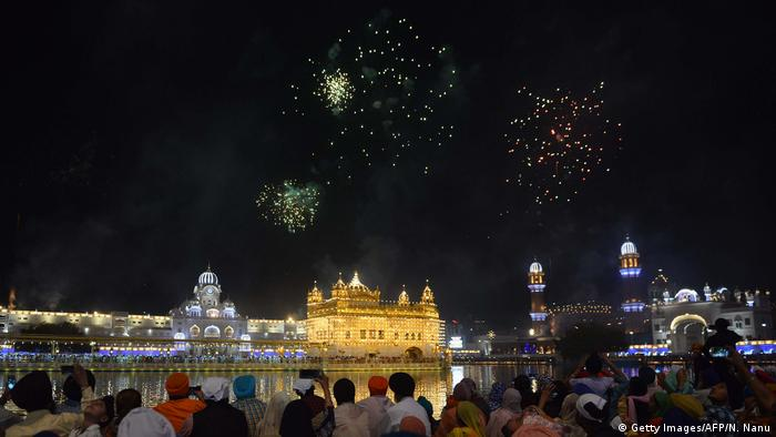 Indian Sikh devotees watch fireworks