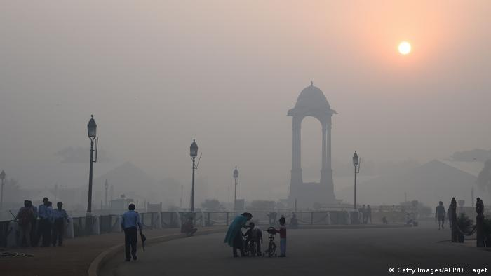 Indian pedestrians walking near the India Gate monument amid heavy smog in New Delhi