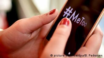 Женщина держит в руках смартфон, на экране которого хэштег #metoo