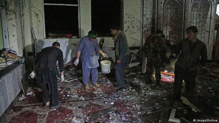 People inspect the aftermath of a suicide bomb attack inside a Shiite mosque in Kabul.