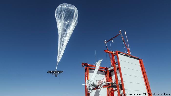 A large, transparent Project Loon balloon with a solar panel attached is launched into the stratosphere from the project site in Nevada