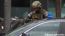 Heavily armed policeman enters a car in Munich (Reuters/M.Dalder)