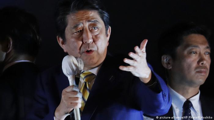 Shinzo Abe addresses a crowd of voters, holding a microphone in one hand and gesturing with the other.
