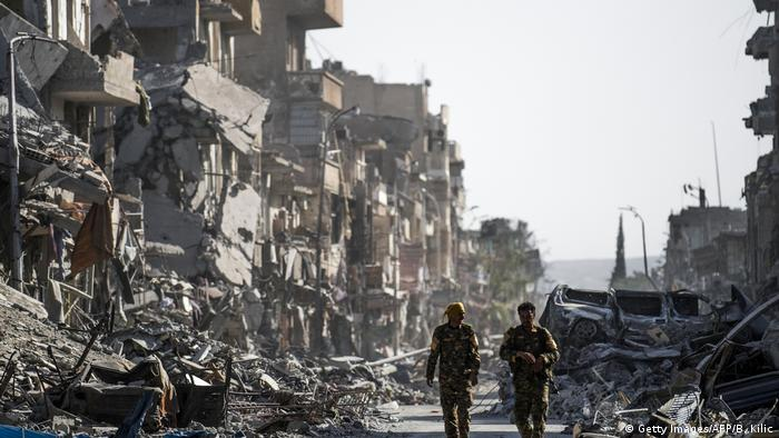Fighters of the Syrian Democratic Forces (SDF) walk down a street in Raqqa