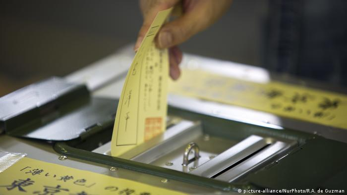 A Japanese voter casts a ballot