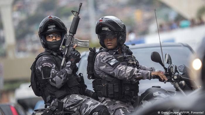 Armed Brazilian police on a motorcycle in a Rio favela