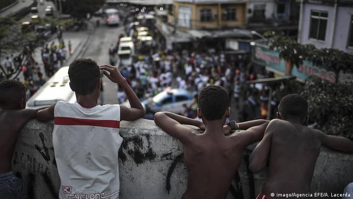 Jóvenes de la Favela Rocinha, en Rio, observan una confrontación entre habitantes y policías. Octubre 2017. (imago/Agencia EFE/A. Lacerda)