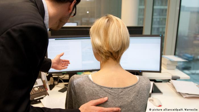 A man places his hand on a woman's back while at work