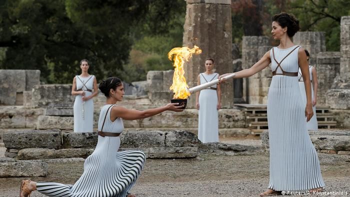 Greek actress Katerina Lehou, playing the role of High Priestess with the flame on the torch during the Olympic flame lighting ceremony