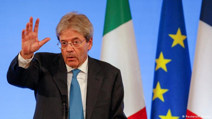 Italian Prime Minister Paolo Gentiloni waves his hand