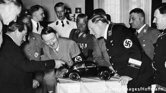 Adolf Hitler admirând, amuzat, modelul Volkswagen cu motorul pe spate, proiectat de Ferdinand Porsche (stânga)