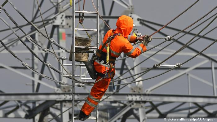 A worker on a ladder repairs a power line (picture-alliance/dpa/U. Anspach)