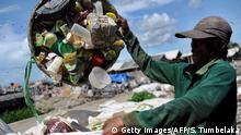 An Indonesia scavenger collects plastic bottles at a garbage dump in Denpasar on the island of Bali on January 28, 2013. AFP PHOTO/Sonny TUMBELAKA (Photo credit should read SONNY TUMBELAKA/AFP/Getty Images)