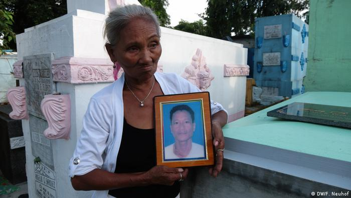 A woman holds up a photograph of her dead son
