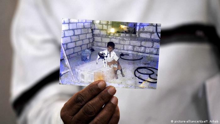 A Yemeni man holds a photo of a child who allegedly died after being injured in a drone strike