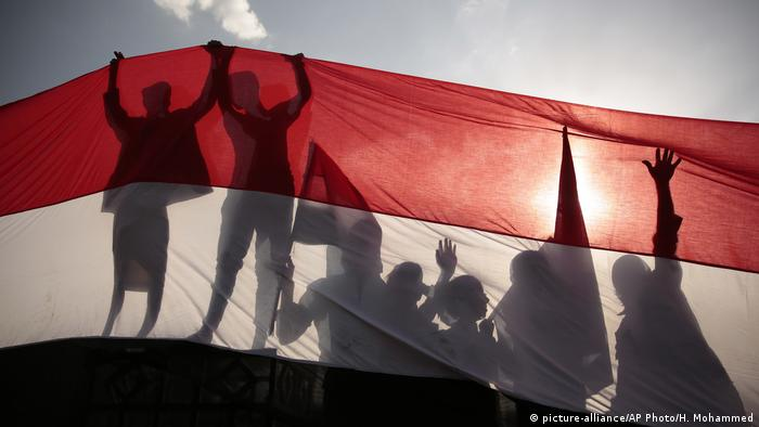 Yemeni men are silhouetted against a large representation of the Yemeni flag.