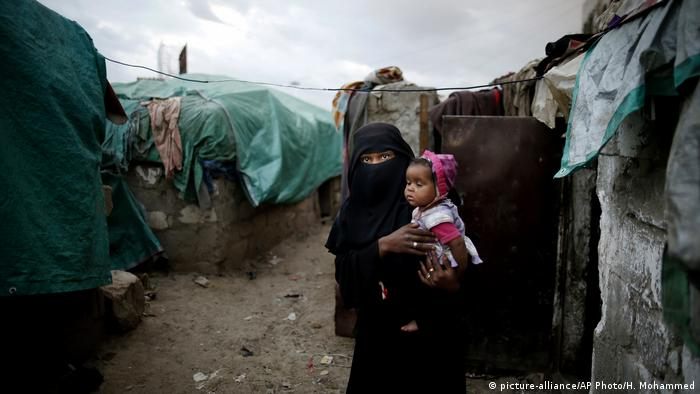 A woman of the Muhammasheen tribe holds her child in a camp for displaced persons