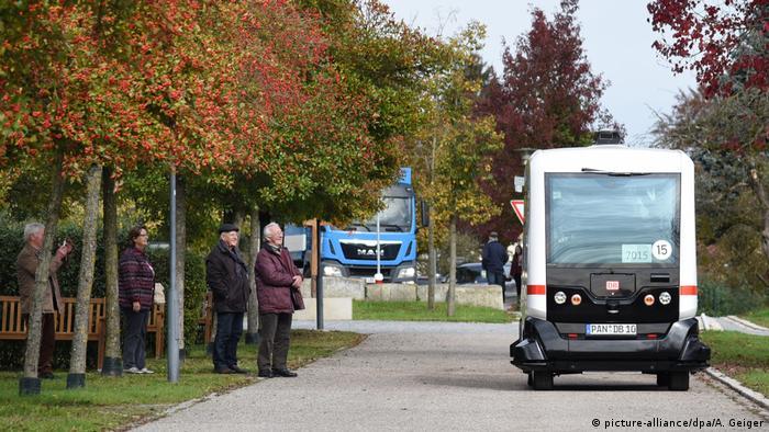 Onlookers watch as an autonomous bus travels through Bad Birnbach
