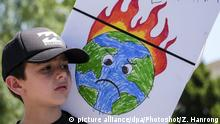 (170601) -- NEW YORK, June 1, 2017 () -- File photo taken on April 29, 2017 shows a child holding a placard during a demonstration against U.S. President Donald Trump's climate policies in Los Angeles, the United States. U.S. President Donald Trump announced U.S. withdrawal from Paris Agreement on climate change on June 1. (/Zhao Hanrong)  