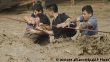 A group of people, stranded in flood waters, hold onto a rope as they wade through flood waters to safety in Lima, Peru, Friday, March 17, 2017. Intense rains and mudslides over the past three days have wrought havoc around the Andean nation and caught residents in Lima, a desert city of 10 million where it almost never rains, by surprise. (AP Photo/Martin Mejia) |