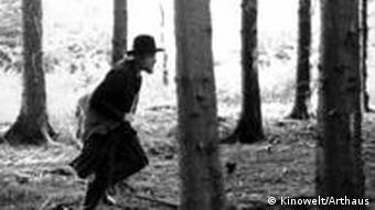 Ein Mann läuft im Wald zwischen den Bäumen