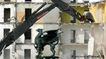 A digger demolishes a building