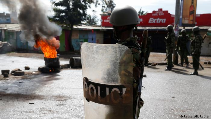A Kenyan police man with a helmet and a protective shield stands in front of burning tires