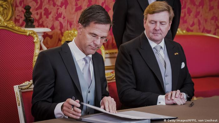 Dutch Prime Minister Mark Rutte signs the royal decree to form a government while sitting next to King Willem-Alexander (Getty Images/AFP/L. van Lieshout)