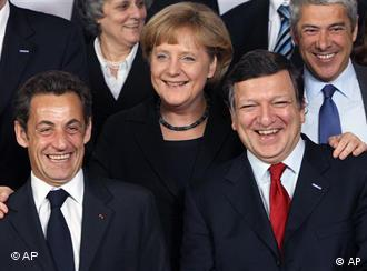 German Chancellor Angela Merkel, center, puts her hands on the shoulders of French President Nicolas Sarkozy, left, and European Commission President Jose Manuel Barroso during a group photo at an EU summit in Brussels, Thursday March 19, 2009. European Union leaders open a summit Thursday fighting over a euro 5 billion recovery plan for new power grids and green energy and raising questions whether the hundreds of billions they are spending is enough to rescue their recession-hit economy. (AP Photo/Geert Vanden Wijngaert)