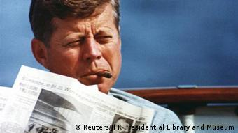 John F. Kennedy smoking a cigar and reading a newspaper