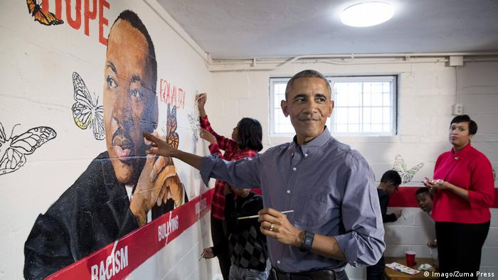 Barack Obama helps to finish a wall painting of Martin Luther King Jr.
